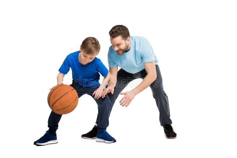 Engendrez avec le fils dans des vêtements sport jouant le basket-ball image stock