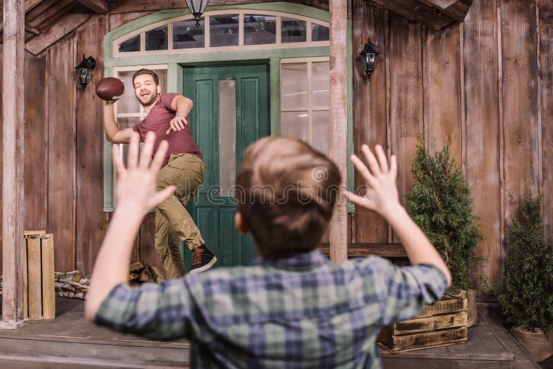 Engendrez avec le petit fils jouant le football américain avec la boule à l'arrière-cour photos libres de droits