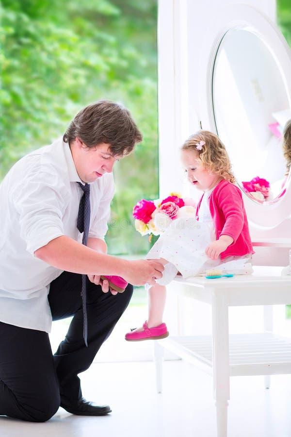 Engendrez avec sa petite fille d'enfant en bas âge mettant sur elle photographie stock