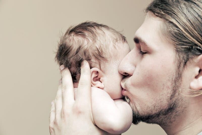 Engendrez avec son jeune bébé le caressant et embrassant sur la joue photos libres de droits