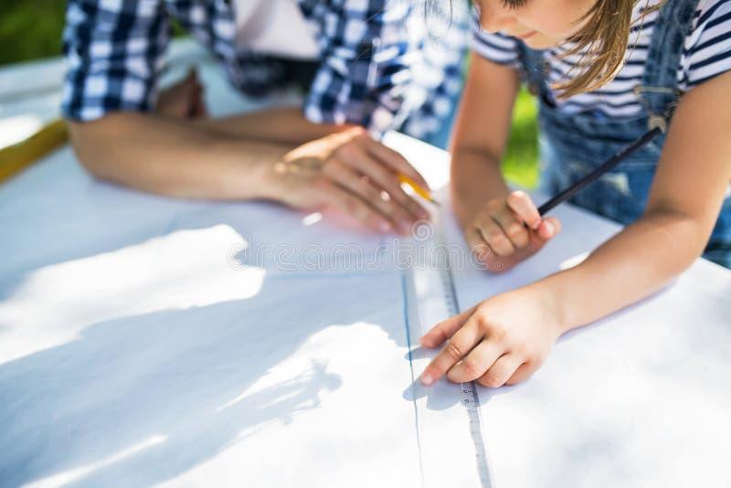 Engendrez avec une petite fille dehors, en prévoyant la volière en bois photographie stock libre de droits