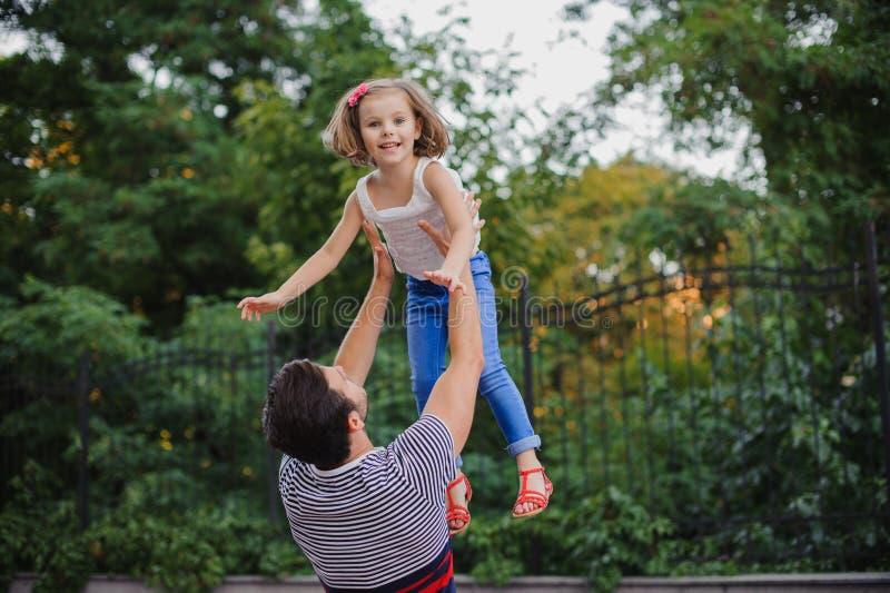 Engendrez avoir l'amusement et jeter sa fille dans le parc images stock