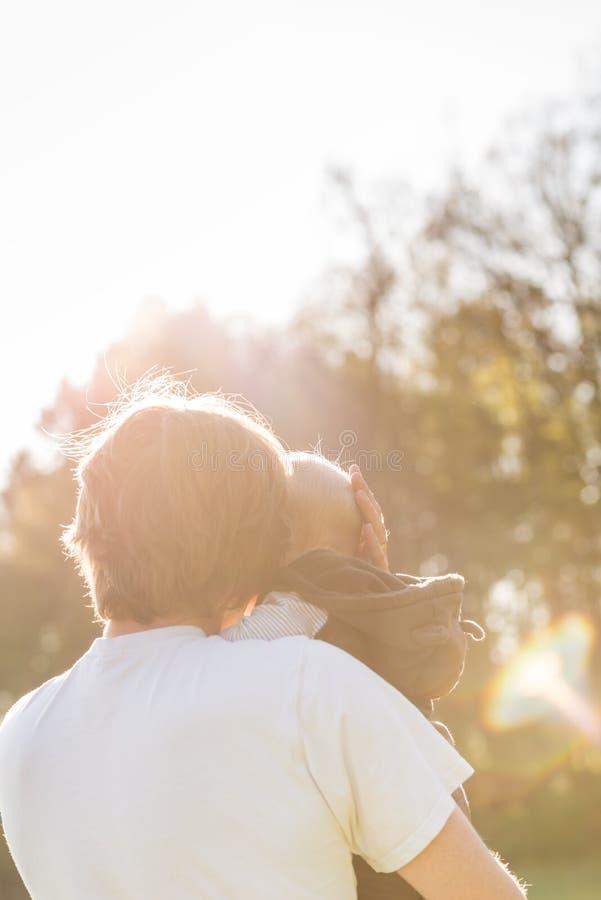 Engendrez bercer son bébé dans des ses bras dans la lueur chaude du soleil photos stock