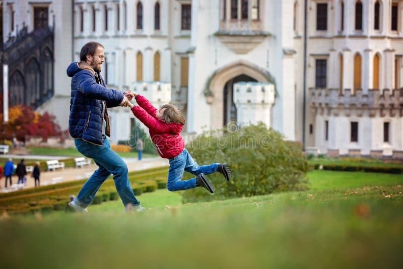 Engendrez, en tournant en cercles son petit fils sur une pelouse devant photo libre de droits