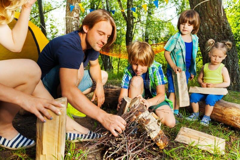 Engendrez enseigner ses enfants à faire un feu de camp photos stock