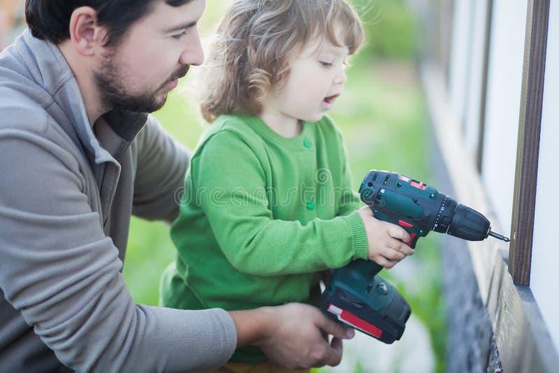 Engendrez et sa petite fille avec le foret, dehors image stock