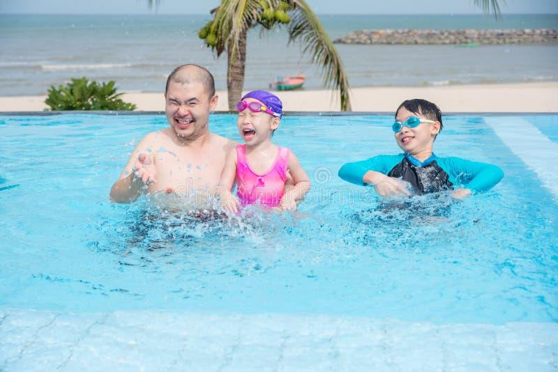 Engendrez et ses enfants jouant dans la piscine extérieure image libre de droits