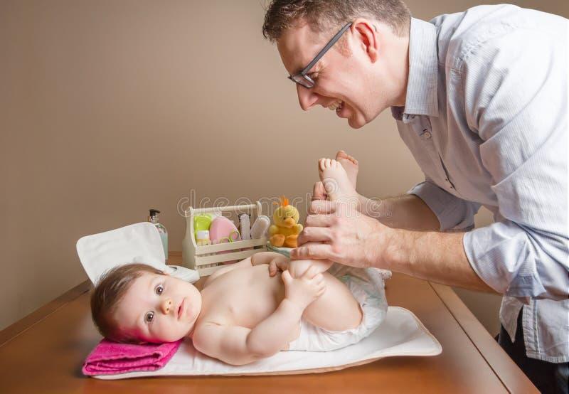 Engendrez jouer avec des pieds de bébé après couche-culotte de changement images stock