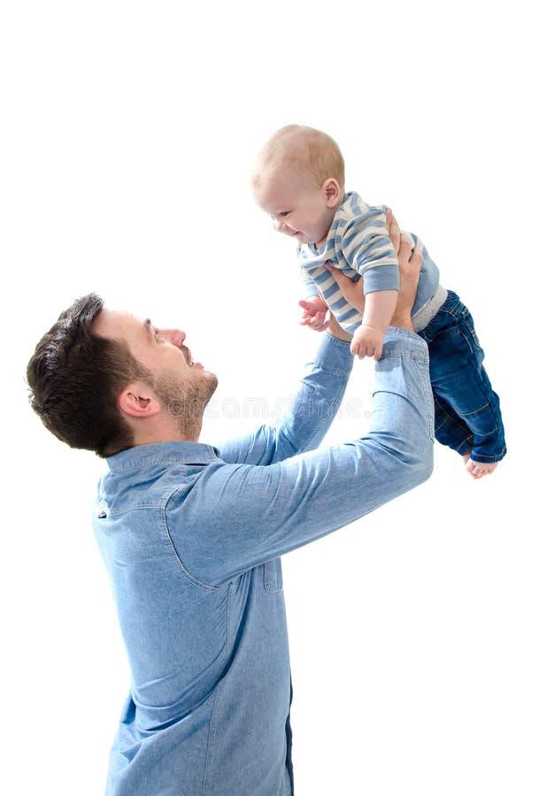 Engendrez l'augmenter son bébé garçon nouveau-né sur ses mains sur le backgro blanc photographie stock libre de droits