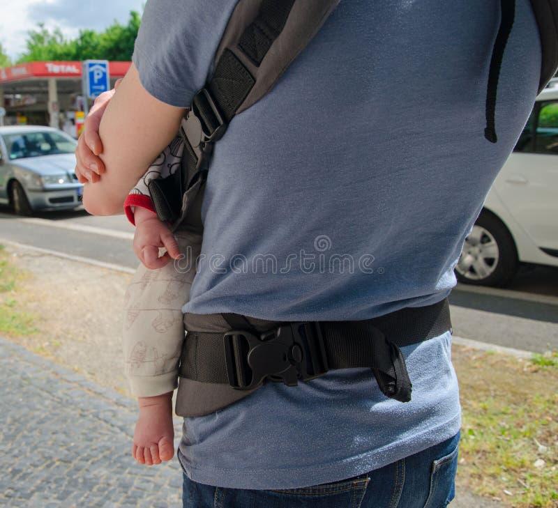 Engendrez l'enfant de prise dans la bride de bébé sur la rue Vue arrière photo libre de droits