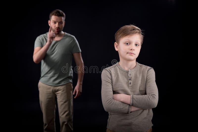 Engendrez la dispute au fils indifférent se tenant avec les bras croisés image stock