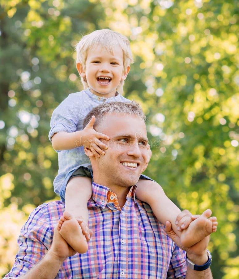 Engendrez la marche en parc avec le fils s'asseyant sur ses épaules photo libre de droits