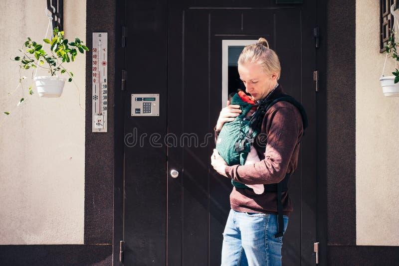 Engendrez le bébé de transport dans la bride ou ergo le sac à dos photos libres de droits