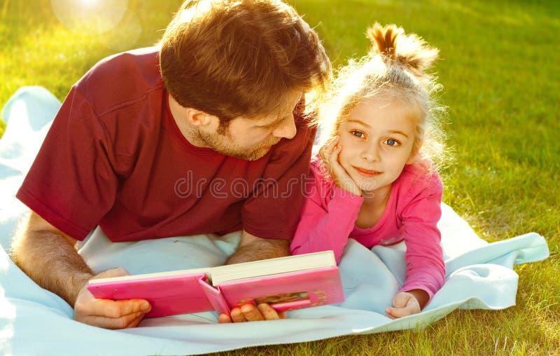 Engendrez lire un livre à sa fille dans le jardin photo stock