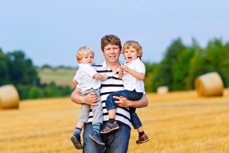 Engendrez tenir deux enfants sur des bras sur le champ de blé en été image stock