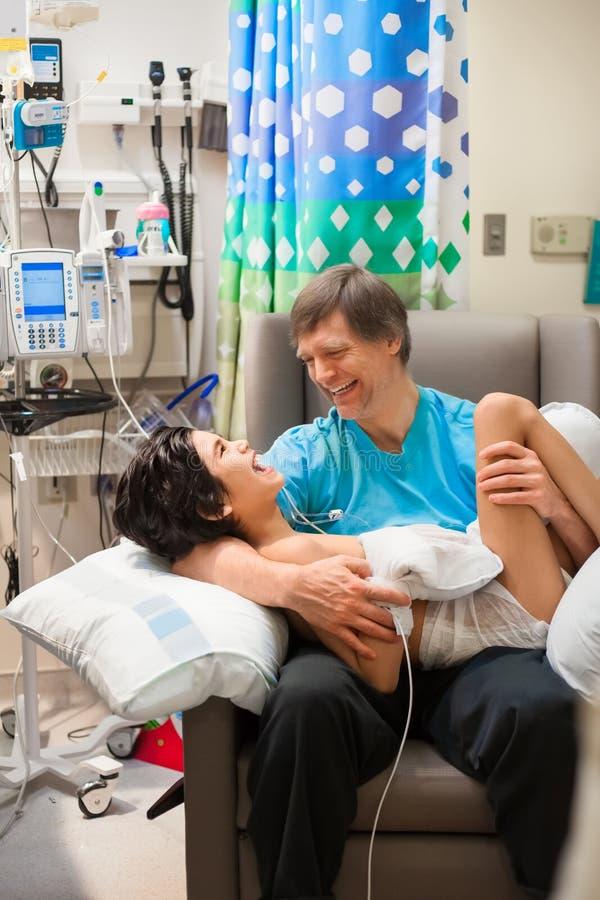 Engendrez tenir le fils malade handicapé sur le recouvrement dans l'hôpital photographie stock