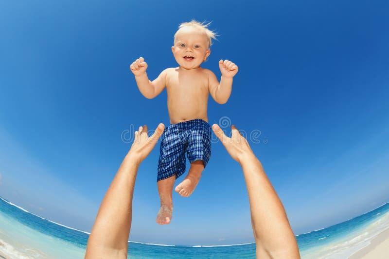 Engendrez trowing vers le haut de la haute dans le ciel un enfant heureux images stock