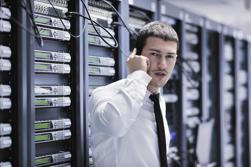 It engeneer talking by phone at network room. Young business man computer science engeneer talking by cellphone at network datacenter server room asking for help
