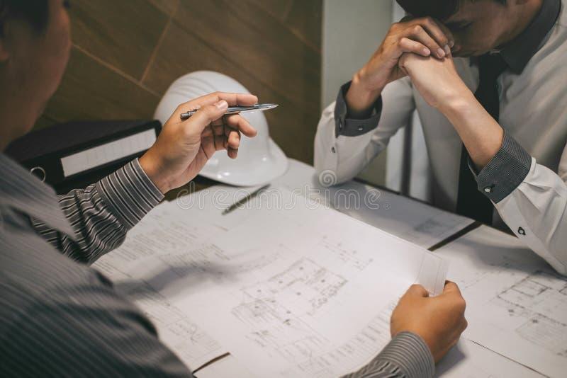 Engenharia ou arquiteto de constru??o para discutir um modelo ao verificar a informa??o na tiragem e no esbo?o, encontrando-se foto de stock