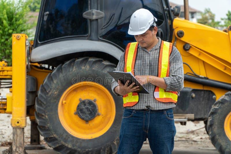 A engenharia que veste uma posição branca do capacete de segurança na frente do backhoe e está usando a tabuleta para a verificaç foto de stock