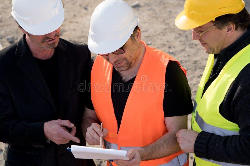Engenheiros civiles que escrevem em um caderno fotografia de stock