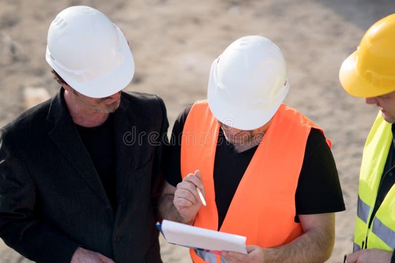 Engenheiros civiles que escrevem em um caderno foto de stock royalty free
