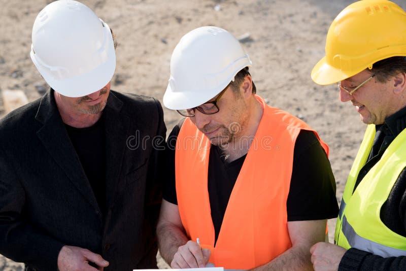 Engenheiros civiles que escrevem em um caderno imagens de stock