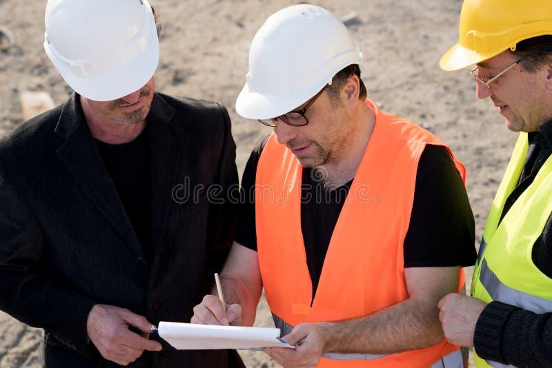 Engenheiros civiles que escrevem em um caderno fotos de stock royalty free