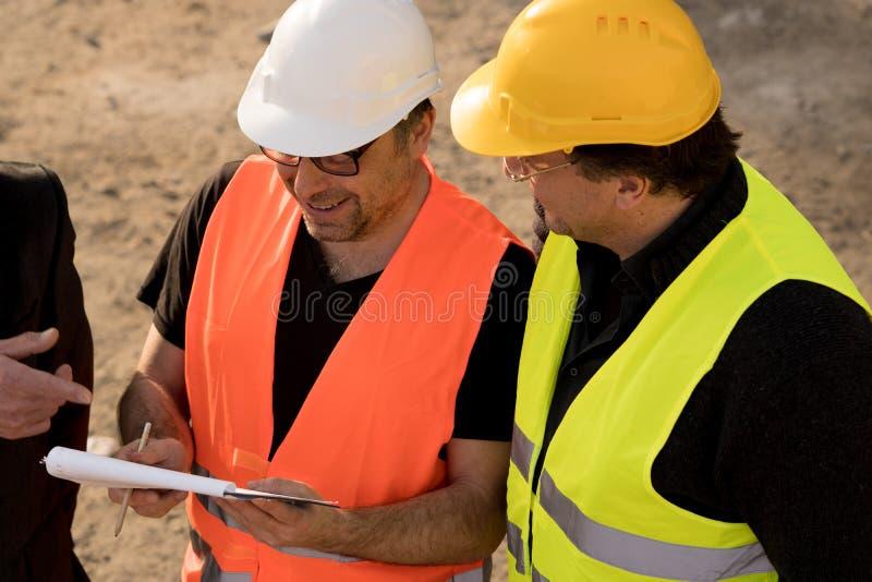 Engenheiros civiles que escrevem em um caderno imagens de stock royalty free
