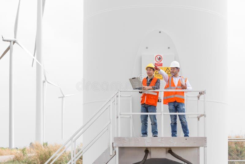 Engenheiros eletrotécnicos e técnico que trabalham na turbina eólica imagens de stock
