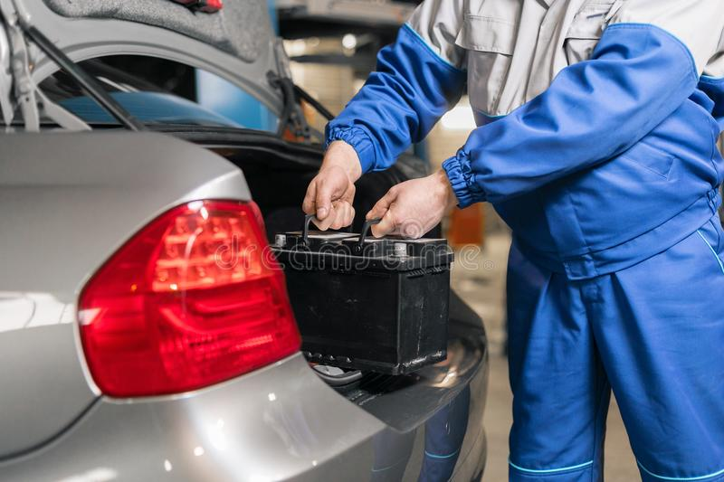 Engine engineer is replacing car battery because car battery is depleted. concept car maintenance stock photography