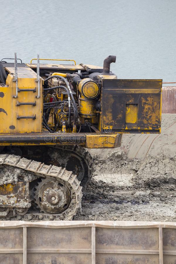 Engine of excavator at barge on the river stock photo