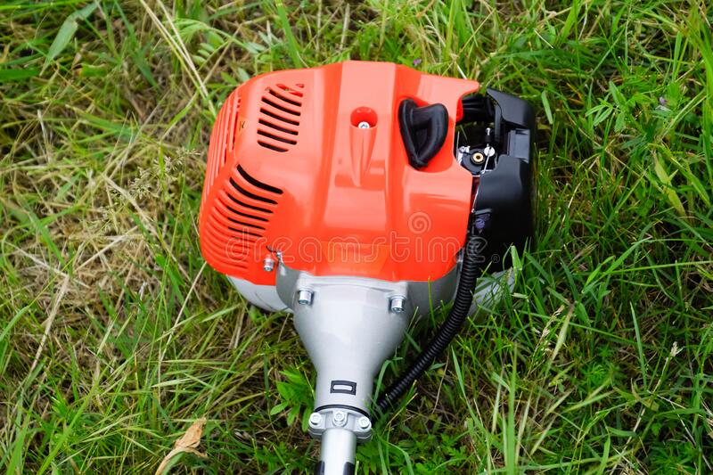 The engine of a gas trimmer lies on the grass. Power part of the trimmer. Trimer gascosis with a leaf for mowing grass and shrubs stock photo