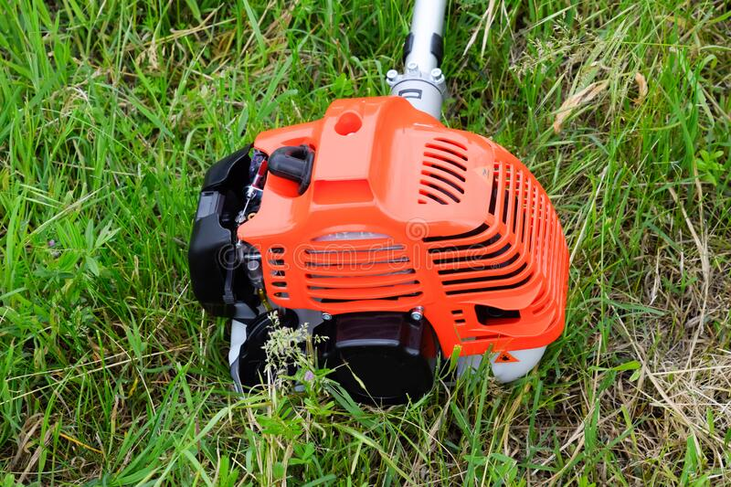 The engine of a gas trimmer lies on the grass. Power part of the trimmer. Trimer gascosis with a leaf for mowing grass and shrubs stock images