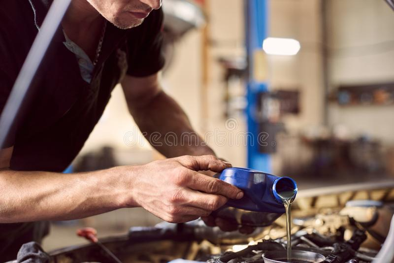 Engine oil changing in auto workshop. Focus on pouring grease from bottle by repairman hands. Maintenance car engine. Engine oil changing in auto workshop. Focus royalty free stock image
