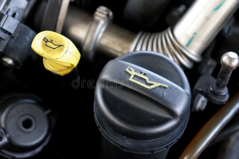 Close up engine oil dipstick and oil cap on a motor vehicle. stock photo