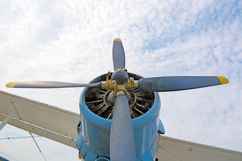 The engine and propeller plane AN2. The engine and propeller plane AN2 close-up on a background of blue sky and clouds. The picture at the low point stock photography