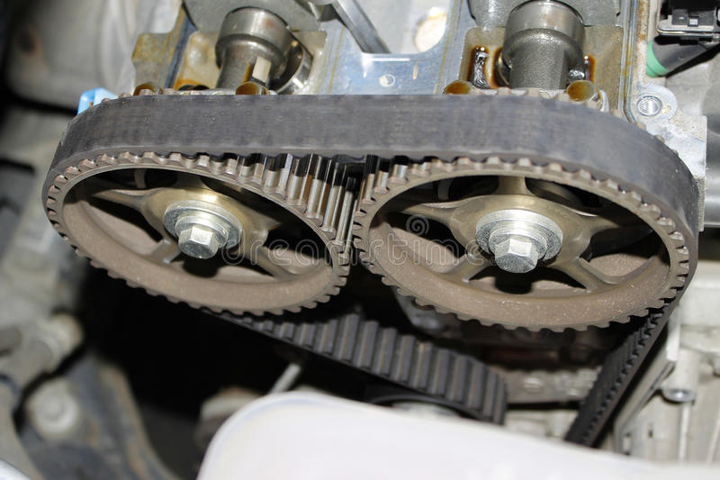 Engine timing belt on camshaft cogwheels. Car combustion engine timing belt on camshaft cogwheels exposed for replacing at auto service royalty free stock photos