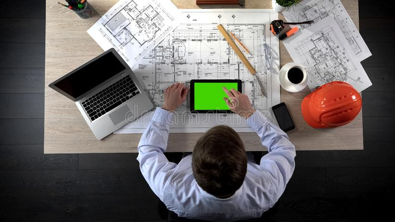 Engineer adding marks to online layout of building project, green screen tablet royalty free stock image