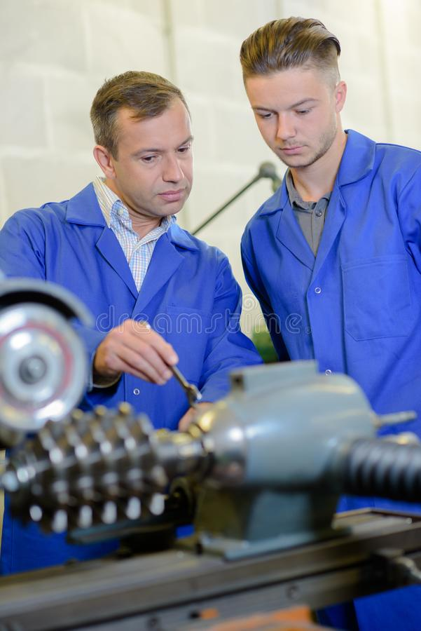 Engineer and apprentice looking at mechanical parts stock photos