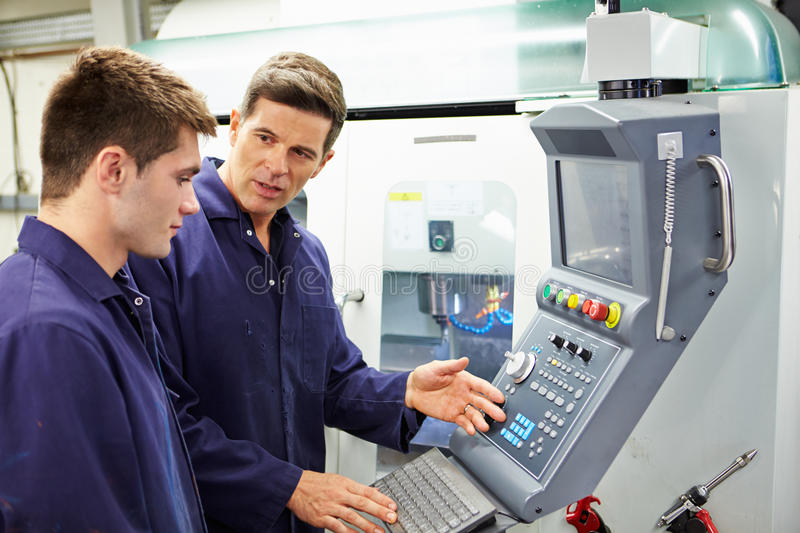 Engineer And Apprentice Using Automated Milling Machine. Having A Discussion royalty free stock image