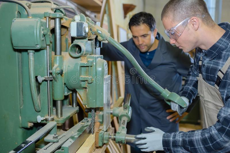 Engineer and apprentice using machinery in factory stock photography
