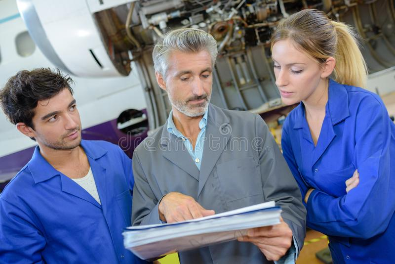 Engineer and apprentices checks aircraft systems royalty free stock photos