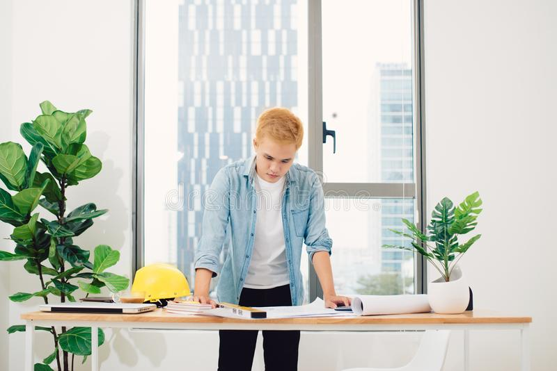 Engineer or architect in blue pullover is working on construction plans. royalty free stock image