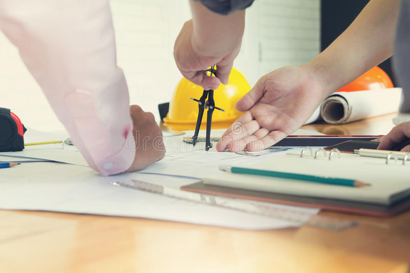 Engineer and Architect concept, Engineer Architects office team working and discussing house plan with blueprints and house mode. L, Vintage Effect royalty free stock photo