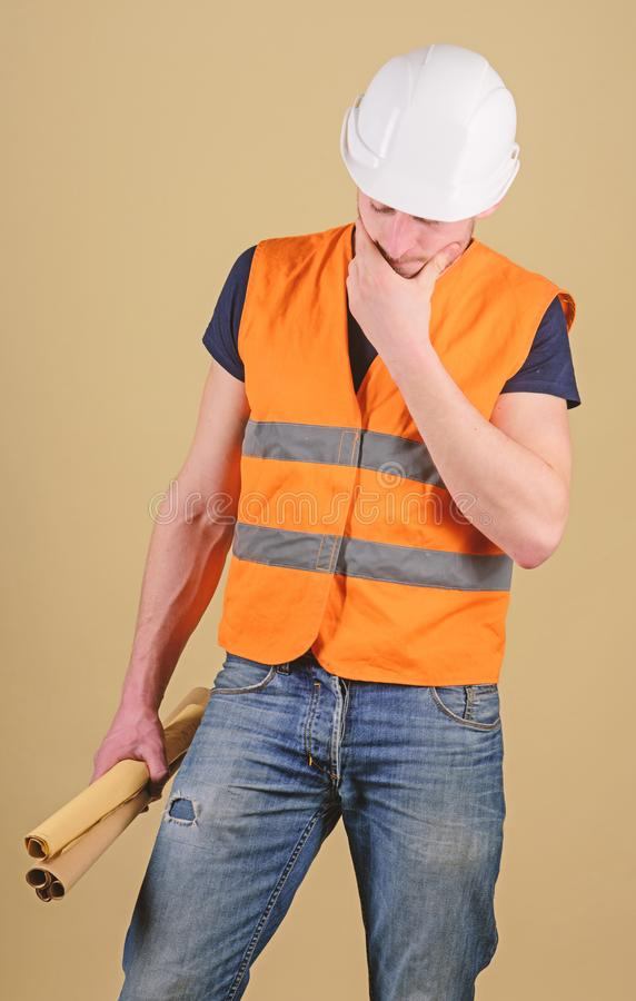 Engineer, architect, labourer, builder on thoughtful face holds old blueprints in hand. Man, foreman in helmet, hard hat royalty free stock photography