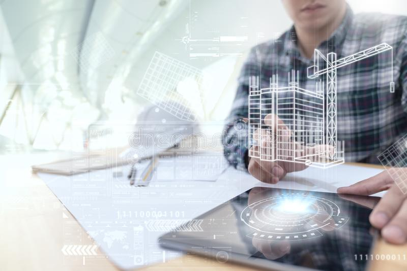 Engineer or Architect looking and touching interface with building design reality virtual technology on computer tablet at modern stock photo