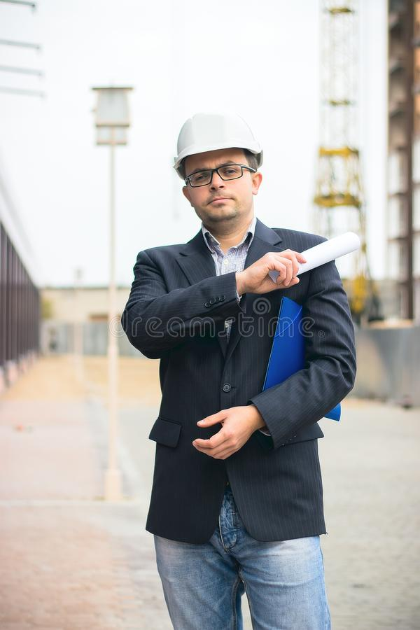 Engineer boss with protective safety helmet checking architectural drawing at construction site. royalty free stock image