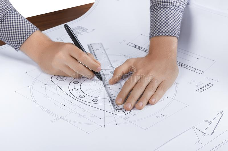 Engineer / architect workplace. Engineer/ architect workplace. Top view on man/male hands making mechanical / architectural sketches of turbine with a pen and stock photo