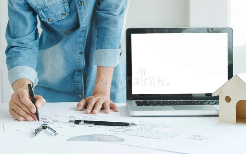 Engineer architects discussing on the table with blueprint with blank screen laptop royalty free stock photo